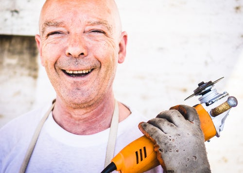 Middle aged man with wrinkles and facial lines holding a drill and smiling before getting his non-surgical facelift