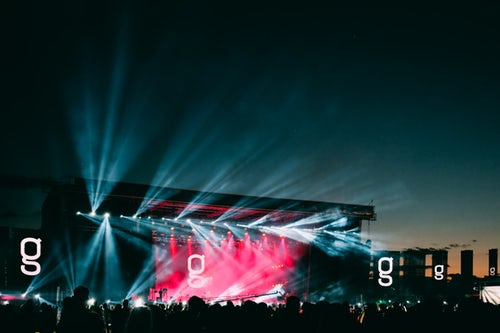 dark sky with a stage shining out bright lights at a music festival