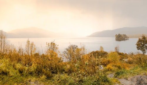 View of Loch Lomond with the sun rising on the horizon from the grassy bank